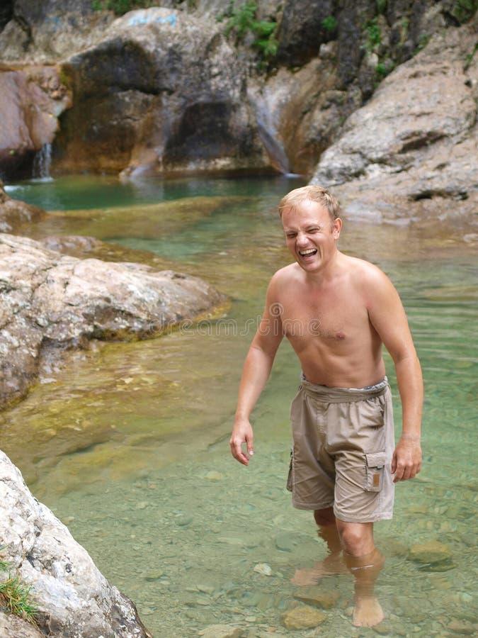 Een jonge mens in koud water stock fotografie