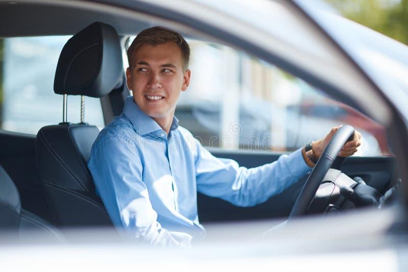 Een jonge mens kwam aan de autoshow een nieuwe auto kiezen royalty-vrije stock fotografie