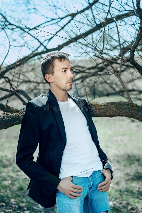 Een jonge mens leunde op de tak van de boom Ik zette mijn hoofd op mijn ellebogen Een jonge mens in een zwart jasje en de blauwe  stock afbeelding