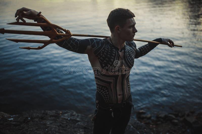Een jonge mens met een drietand in zijn schouders tegen de achtergrond van water royalty-vrije stock foto