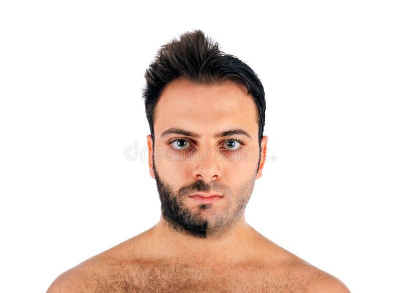 Een jonge mens met een baard op de helft van het gezicht stock afbeelding