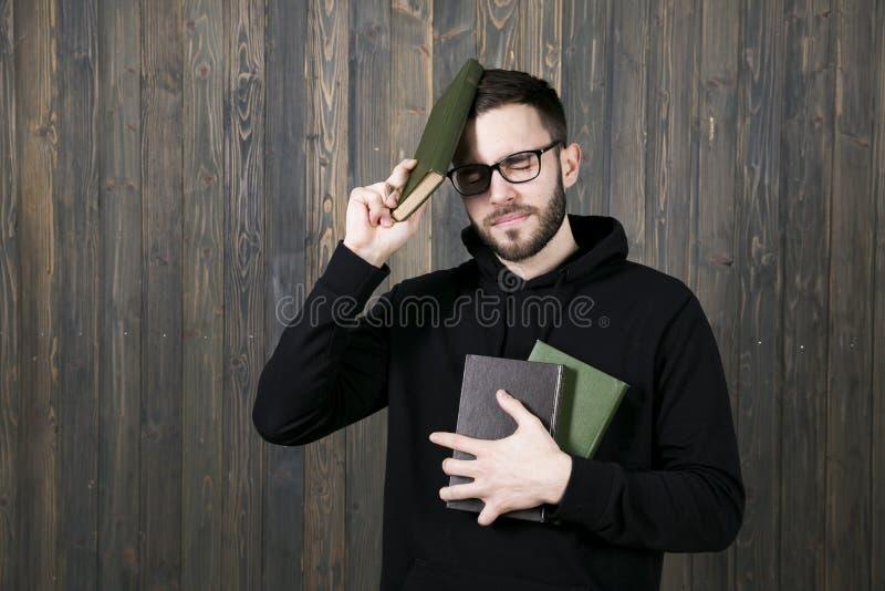 Een jonge mens met glazen en zwarte kleren met boeken in één han stock afbeeldingen