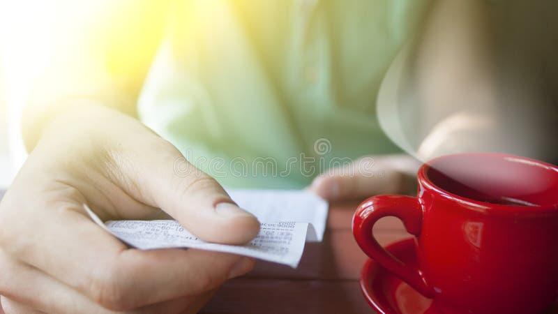 Een jonge mens onderzoekt de rekening in een koffie op een Zonnige de zomerochtend stock foto's