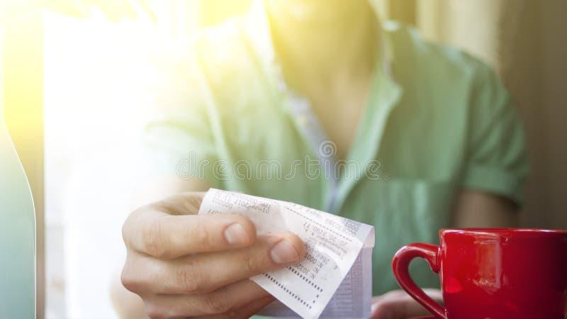 Een jonge mens onderzoekt de rekening in een koffie op een Zonnige de zomerochtend stock afbeelding
