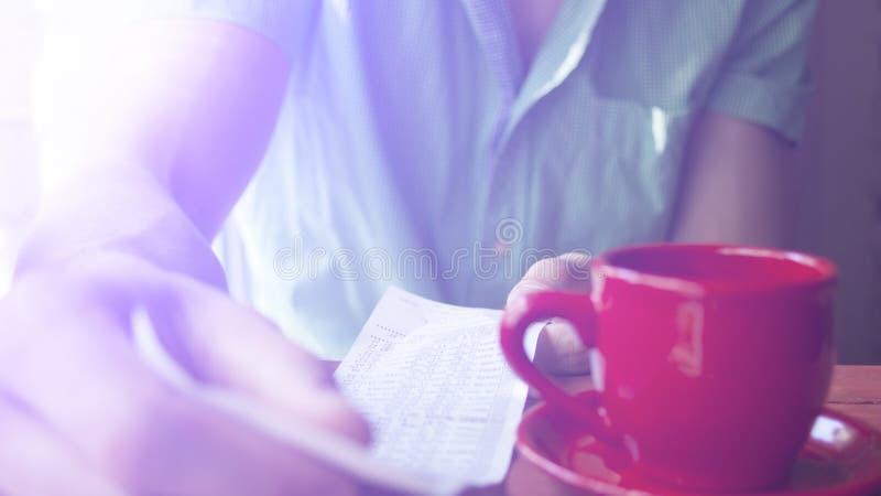 Een jonge mens onderzoekt de rekening in een koffie op een Zonnige de zomerochtend royalty-vrije stock foto