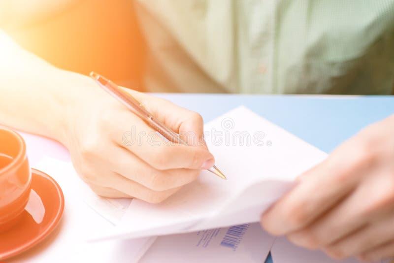 Een jonge mens onderzoekt en ondertekent de brief Het concept correspondentie royalty-vrije stock afbeelding