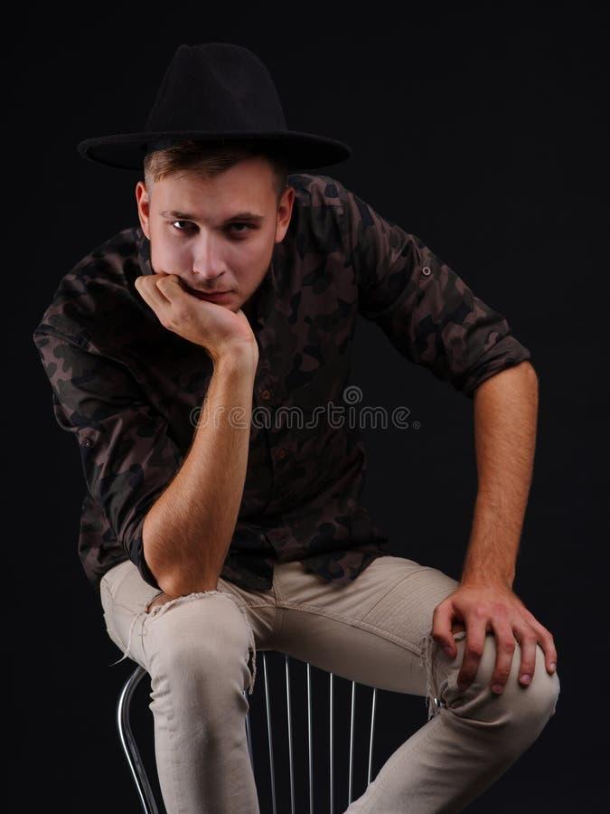 Een jonge mens op een zwarte achtergrond in een hoed denkt na royalty-vrije stock fotografie
