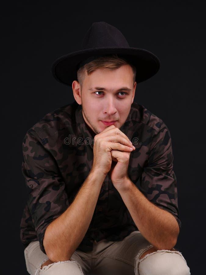 Een jonge mens op een zwarte achtergrond in een hoed kijkt weg stock fotografie