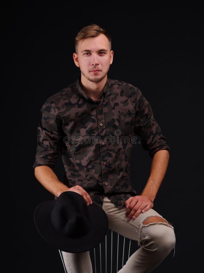 Een jonge mens op een zwarte achtergrond met een hoed in zijn handen op een stoel royalty-vrije stock foto's