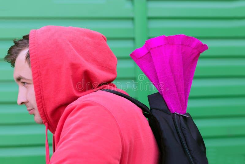 Een jonge mens in een rood jasje met een kap op zijn hoofd en een rugzak op zijn rug draagt een gift in een helder pakket aan van royalty-vrije stock foto