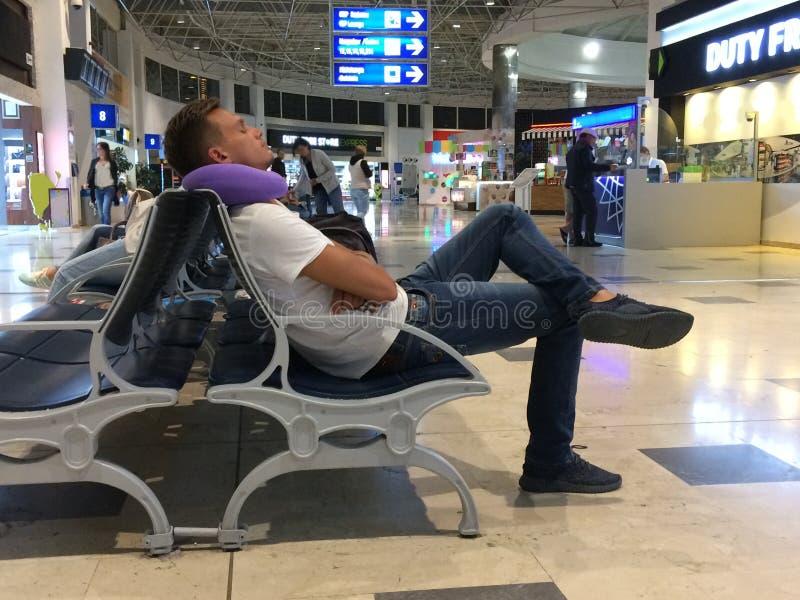 Een jonge mens slaapt op een stoel bij de luchthaven, zettend een pil royalty-vrije stock afbeelding