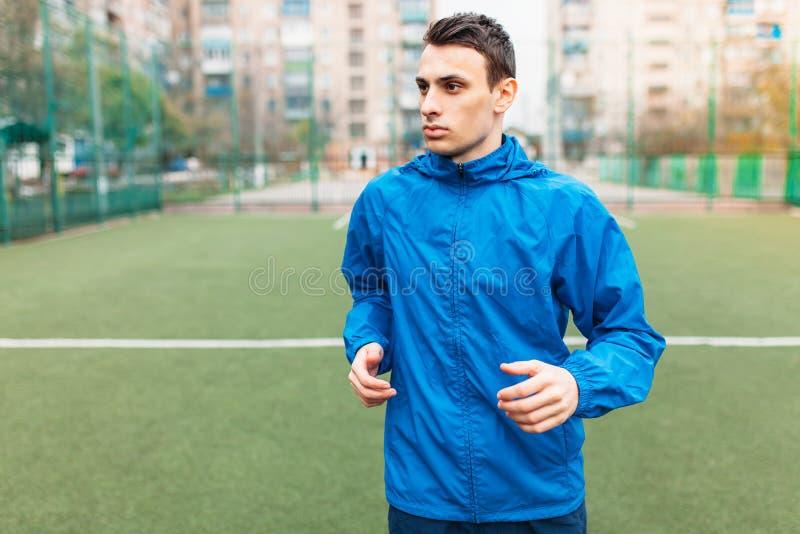 Een jonge mens speelt sporten, loopt op het voetbalgebied De kerel werkt in de open, verse lucht stock afbeeldingen