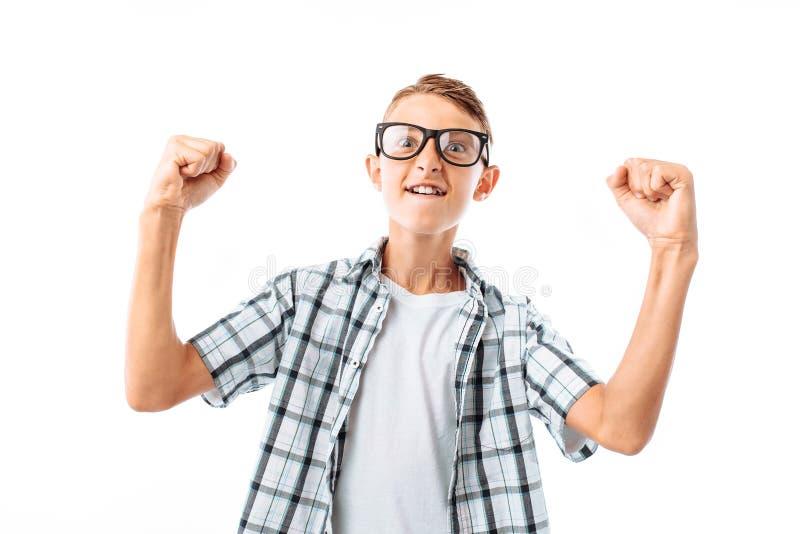 Een jonge mens verheugt zich bij de overwinning, in de Studio op een witte achtergrond, exemplaarruimte links van kerel royalty-vrije stock fotografie