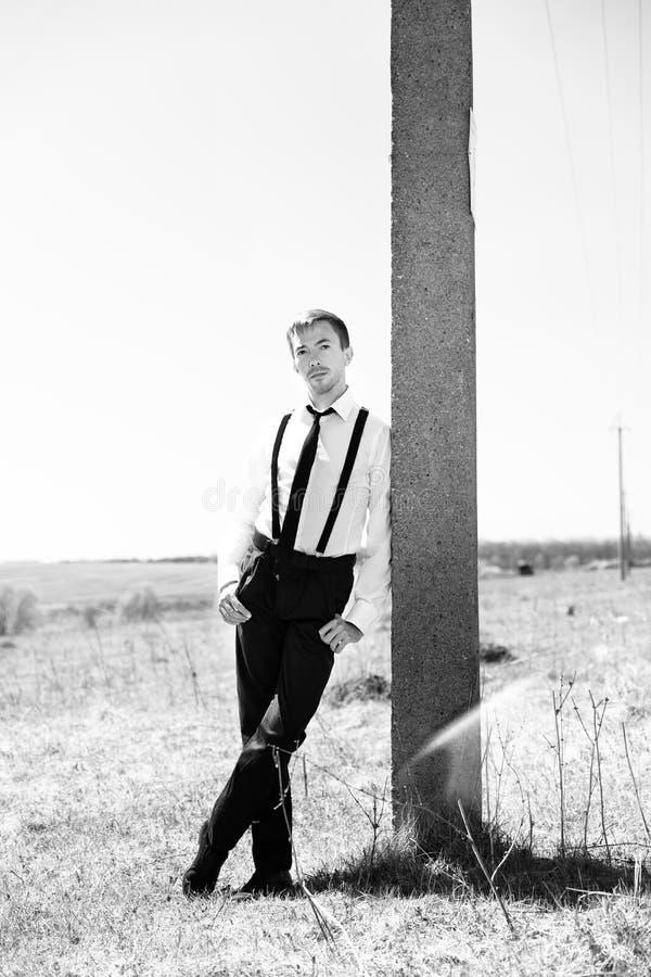 Een jonge mens in een wit overhemd, een zwarte broek en bretels bevindt zich leunend tegen een post royalty-vrije stock afbeeldingen