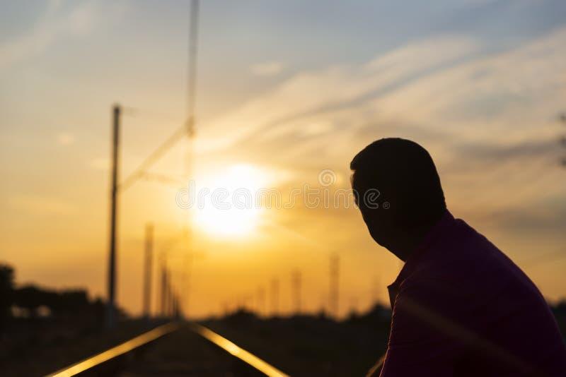Een jonge mens zit op de sporen en onderzoekt de afstand bij zonsondergang stock fotografie