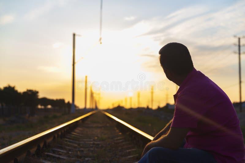 Een jonge mens zit op de sporen en onderzoekt de afstand bij zonsondergang royalty-vrije stock foto