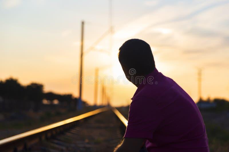 Een jonge mens zit op de sporen en onderzoekt de afstand bij zonsondergang royalty-vrije stock afbeeldingen