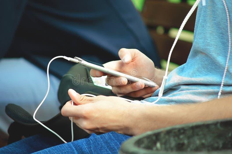 Een jonge mens zit op de straat en gebruikt een smartphone met hoofdtelefoons royalty-vrije stock afbeelding