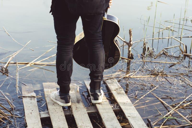 Een jonge mens in zwarte kleren met een gitaar in zijn hand bevindt zich op een dilapidated brug op de rivierbank royalty-vrije stock afbeelding