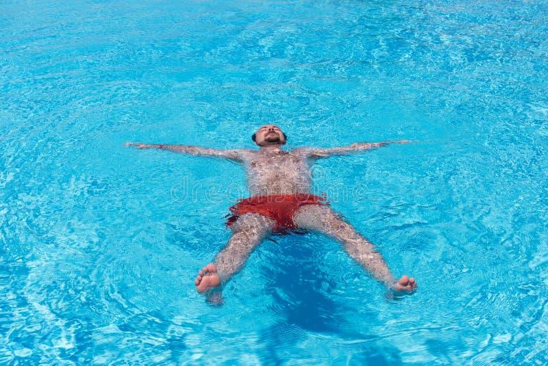 Een jonge mens zwemt in de pool, bewapent uitgestrekt stock foto's