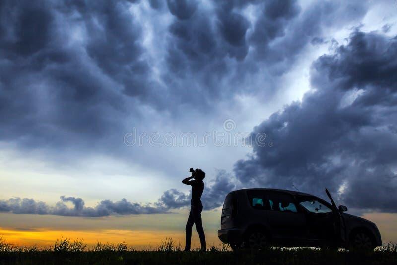 Een jonge mensen alleen holding zijn camera tegen een dramatische hemel bij schemer royalty-vrije stock afbeeldingen