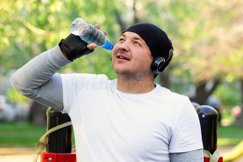 Een jonge mensenatleet met hoofdtelefoons op zijn hoofd drinkwater na een harde training op de straat Kerelglimlachen die genoege stock afbeeldingen