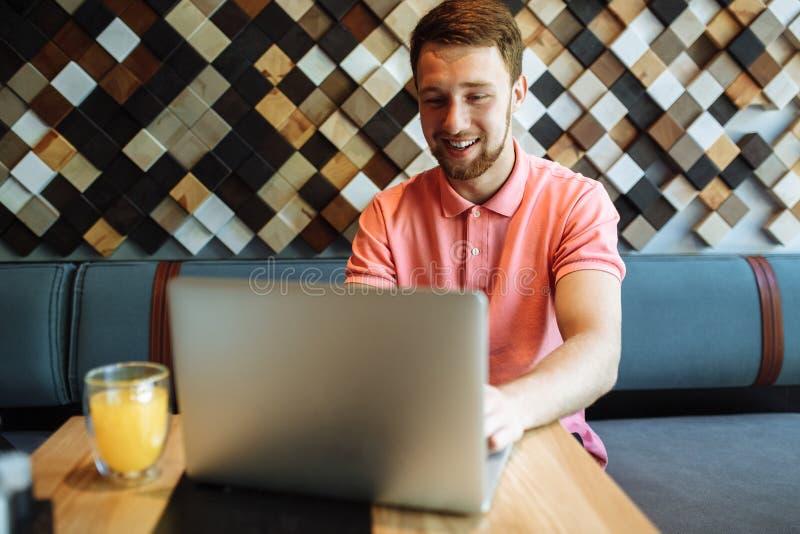 Een jonge mensenzitting in een koffie met laptop, het werken, die hipster online winkelen royalty-vrije stock foto