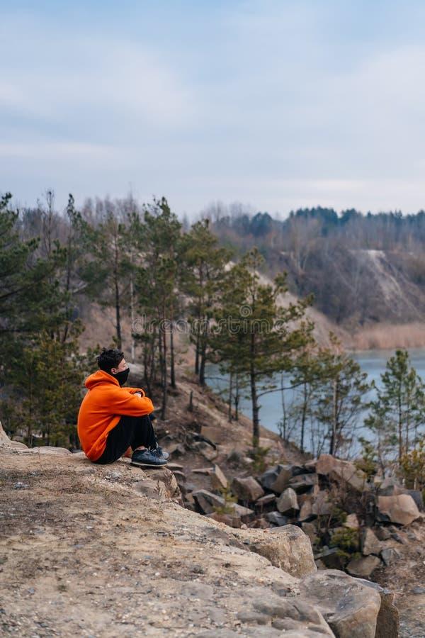 Een jonge mensenzitting op de rand van een klip stelt voor de camera stock foto's