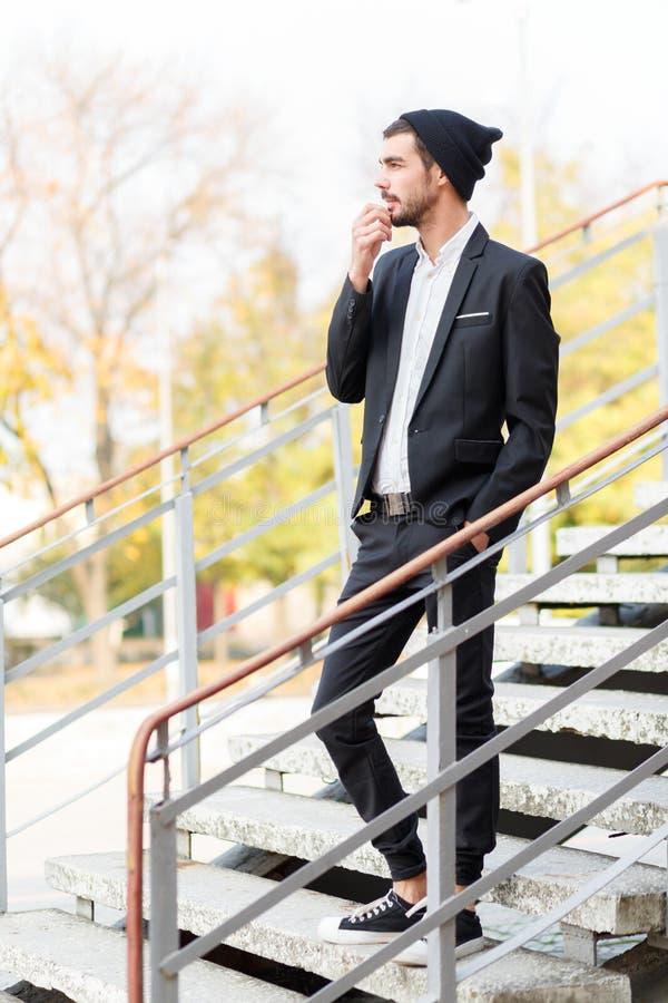 Een jonge modieuze kerel met een peinzende blik is op de stappen outdoors royalty-vrije stock foto's