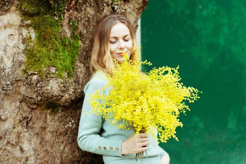 Een jonge modieuze vrouw is het glimlachen, houdend een heden in haar hand een boeket van verse mimosabloemen royalty-vrije stock afbeelding