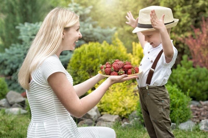 Een jonge moeder behandelt haar rijpe geurige aardbeien van de babyzoon stock afbeeldingen