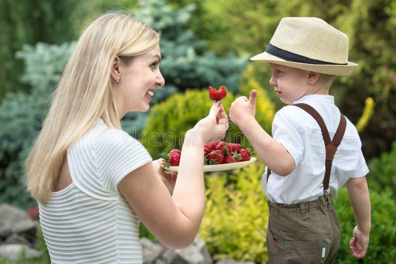Een jonge moeder behandelt haar rijpe geurige aardbeien van de babyzoon stock foto