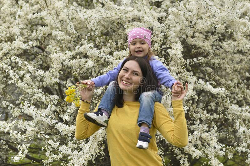 Een jonge moeder heeft haar weinig dochter op haar schouders gezet en met haar in de bloeiende tuin gespeeld stock afbeelding