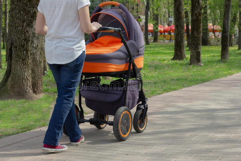 Een jonge moeder loopt met een babywandelwagen in een de zomerpark op een zonnige dag stock afbeelding