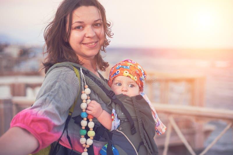 Een jonge moeder is op het strand met haar baby in een slinger royalty-vrije stock foto
