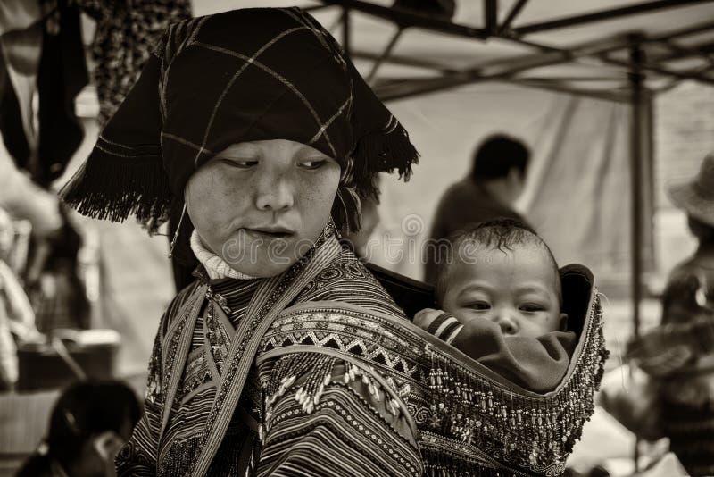 Een jonge moeder vervoert haar zuigeling terug op haar in Sapa, Vietnam stock afbeeldingen