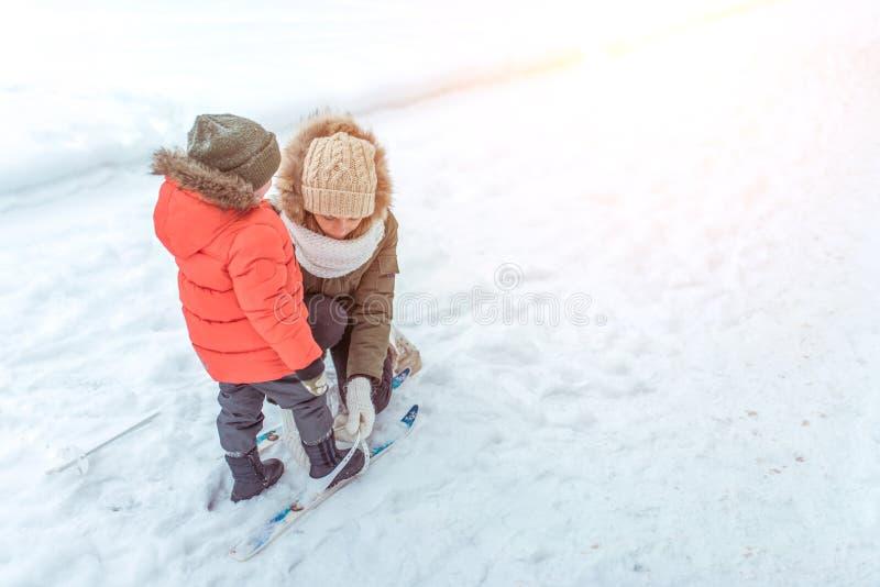 Een jonge moeder een vrouw maakt haar skis, een kleine zoon, een jongen van recht 3 jaar De winter op straat in park, achtergrond stock afbeeldingen
