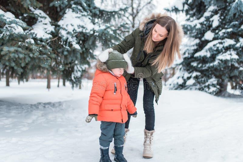 Een jonge moeder, een vrouw schudt van de sneeuw van een jongen 4-6 jaar oude zoon In de winter in het park buiten Het geven voor stock foto