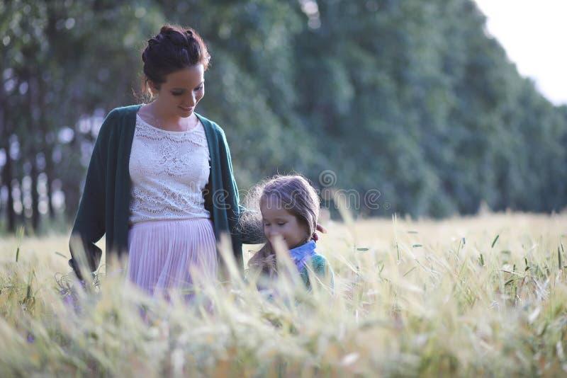 Een jonge moedergang op tarwegebieden royalty-vrije stock fotografie