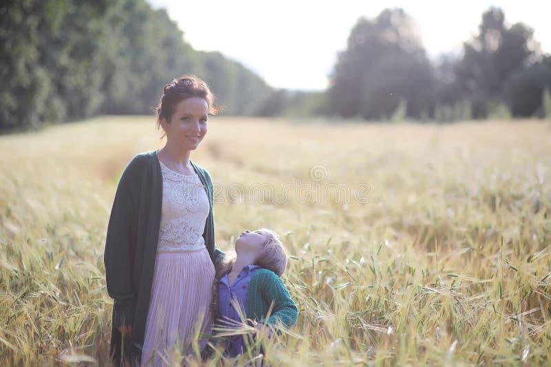 Een jonge moedergang op tarwegebieden royalty-vrije stock foto's