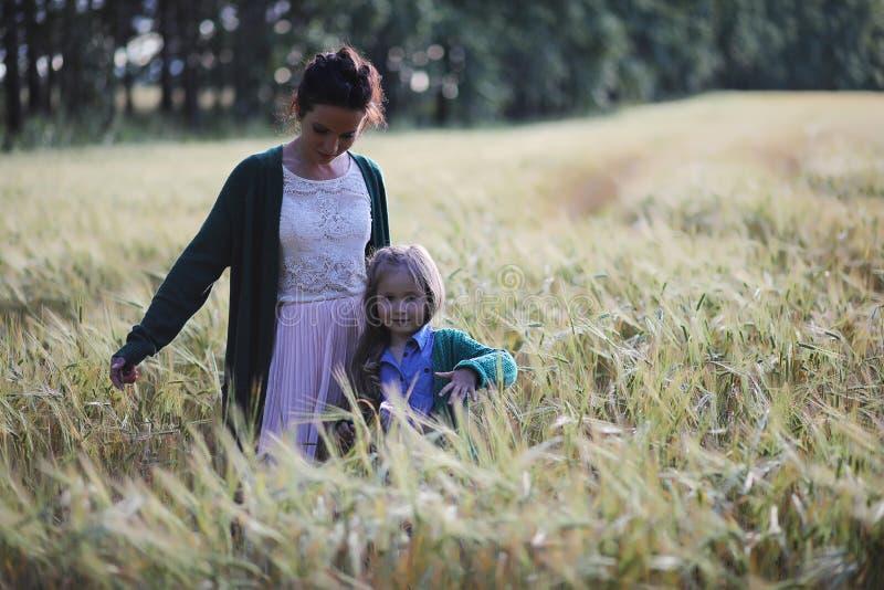Een jonge moedergang op tarwegebieden stock afbeeldingen
