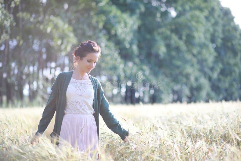 Een jonge moedergang op tarwegebieden stock foto's