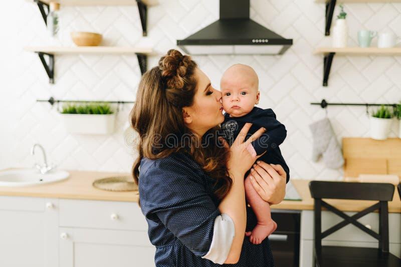 Een jonge mooie Kaukasische vrouwenzitting bij de keukenlijst en het kussen van haar snoepje weinig baby royalty-vrije stock afbeeldingen
