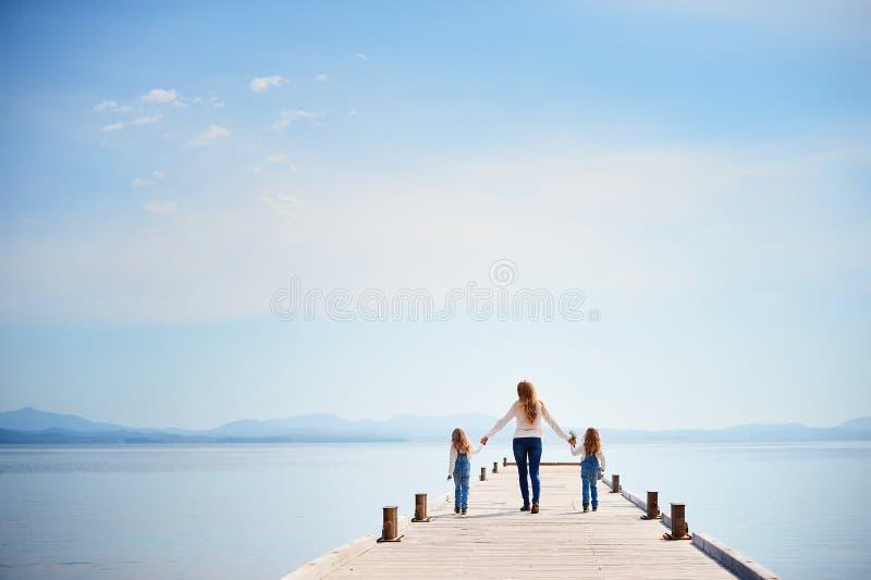 Een jonge mooie moeder met haar tweelingdochters loopt alon stock fotografie