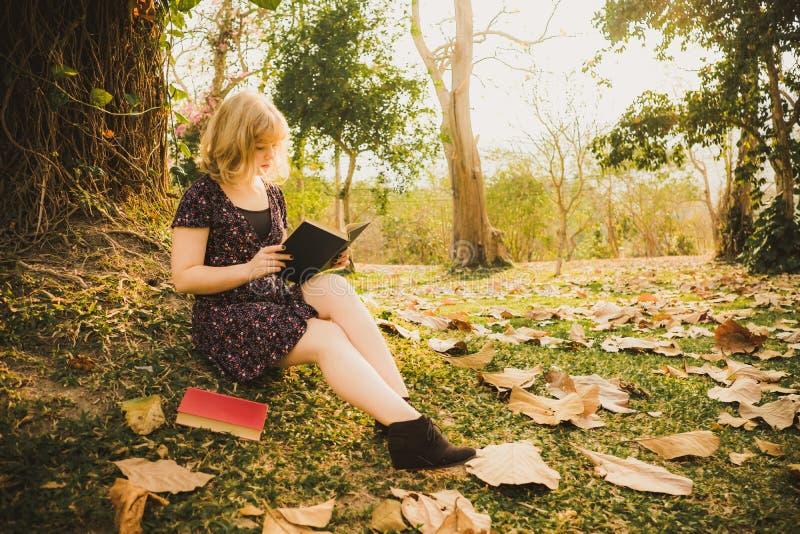 Een jonge mooie vrouw die een boek in het park lezen stock foto