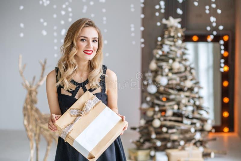 Een jonge mooie vrouw houdt een heden en het glimlachen Concept Gelukkig Kerstmis en Nieuwjaar, de winter, partij royalty-vrije stock afbeeldingen