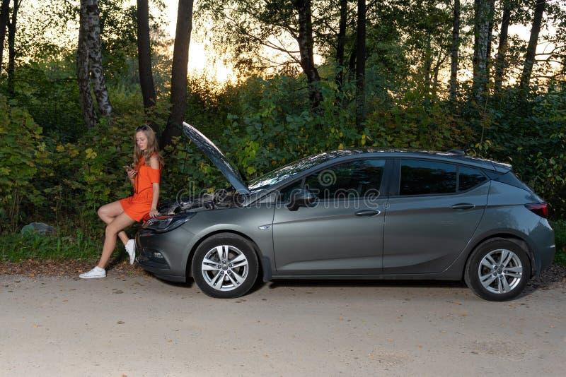Een jonge mooie vrouw met een gebroken auto die mobiele telefoon met behulp van aan vraaghulp op kant van de weg royalty-vrije stock fotografie