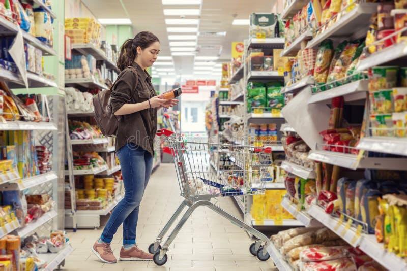 Een jonge mooie vrouw rolt een kruidenierswinkelkar en kiest producten in de supermarkt stock foto