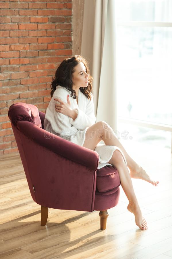 Een jonge mooie vrouw in een witte badstofpeignoir zit als voorzitter en kijkt uit het venster Achtergrond, rode bakstenen muur stock foto's