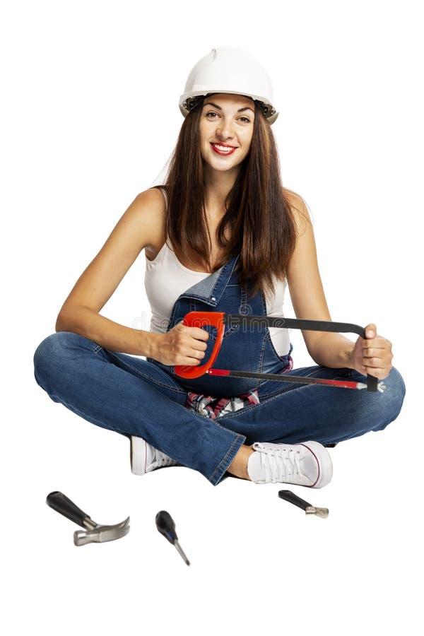 Een jonge mooie zwangere vrouw in een bouwhelm zit op de vloer met dichtbij opgemaakte hulpmiddelen en glimlacht royalty-vrije stock foto